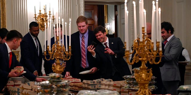 Guests attending a reception for the Clemson Tigers grab fast food sandwiches in the State Dining Room of the White House in Washington, Monday, Jan. 14, 2019. (AP Photo/Susan Walsh)