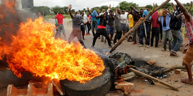 "In this Tuesday, Jan. 15, 2019 file photo, protestors gather near a burning tire during a demonstration over the hike in fuel prices in Harare, Zimbabwe. 2019 is already a busy year for internet shutdowns in Africa, with governments ordering cutoffs as soon as a crisis appears. Zimbabwe ordered a ""total internet shutdown"" in recent days during protests over a dramatic fuel price increase and a resulting deadly crackdown."
