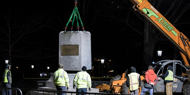 """The first and largest piece of the remnants of a Confederate statue known as """"Silent Sam"""" is lifted before being transported to the bed of a truck early Tuesday, Jan. 15, 2019 on the campus of the University of North Carolina in Chapel Hill, N.C. The last remnants of the statue were removed at the request of UNC-Chapel Hill Chancellor Carol Folt, who also announced her resignation in a move that increases pressure on the system's board of governors to give up on plans to restore the monument. (Julia Wall/The News & Observer via AP)"""