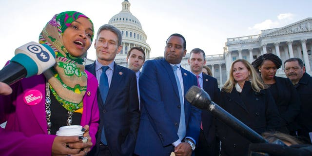 Rep. Ilhan Omar, D-Minn., left, Rep. Mike Levin, D-Calif., Rep. Christopher Pappas, D-N.H., Rep. Joe Neguse, D-Colo., and other freshmen member of the House of Representatives speak about the government shutdown on Capitol Hill, Tuesday, Jan. 15, 2019 in Washington. (AP Photo/Alex Brandon)