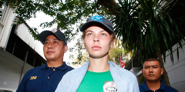 Thai Immigration police officers escort Belarusian model Anastasia Vashukevich, center, from the Immigration Detention Center towards a vehicle to take her to an airport for deportation, in Bangkok, Thailand, Thursday, Jan. 17, 2019. Thai police says it will deport Vashukevich who claimed that she had evidence of Russian involvement in helping elect Donald Trump as U.S. president after she pleaded guilty in a case related to holding a sex training seminar in Thailand. (AP Photo/Sakchai Lalit)