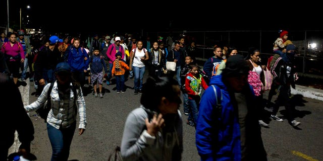 Honduras migrants walk cross the border bridge between Mexico and Guatemala without authorities registration in Ciudad Hidalgo, Mexico, Friday, Jan. 18, 2019.