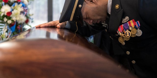 Sgt. Jose Burgos pauses for a moment at the casket of Vietnam veteran Peter Turnpu as several hundreds gather for a funeral Friday, Jan. 18, 2019 in Wrightstown, N.J. (Associated Press)