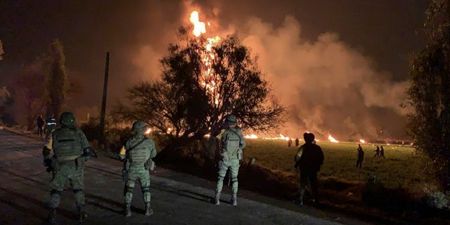 Mexican soldiers guard the area near an oil pipeline explosion in Tlahuelilpan, Hidalgo state, Mexico, Friday, Jan. 18, 2019.