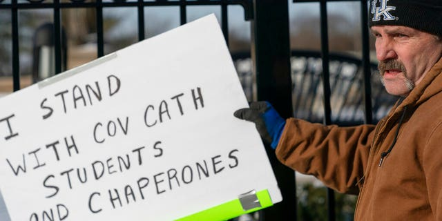 A man places a sign showing support for the students of Covington Catholic Catholic High School in front of the Catholic Diocese of Covington in Covington, Ky., Tuesday, Jan 22, 2019. (AP Photo/Bryan Woolston)