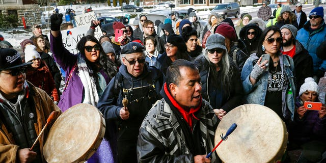 A protestor leads a Native American prayer with a traditional drum outside the Catholic Diocese of Covington Tuesday, Jan. 22, 2019, in Covington, Ky. The diocese in Kentucky has apologized after selectively edited videos emerged showing students from Covington Catholic High School seeming to mock Native Americans outside the Lincoln Memorial on Friday after a pro-life rally in Washington. Later, unedited videos showed the students themselves were harassed and approached by other activists. (AP Photo/John Minchillo)