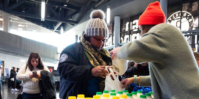 TSA worker Amelia Williams is given a bottle of milk at a food bank for government workers affected by the shutdown, Tuesday, Jan. 22, 2019, in the Brooklyn borough of New York. (AP Photo/Mark Lennihan)