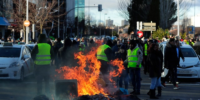 Striking Spanish taxi drivers demand more rules for app-based driving services blocking access to a trade exhibition center in Madrid, where a major tourism fair begins Wednesday