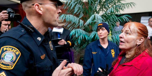 Reese Greer, right, a furloughed census worker, argues with a Lexington police officer outside U.S. Sen. Mitch McConnell's office in Lexington, Ky., Wednesday, Jan 23, 2019, during a government shutdown protest. (AP Photo/Bryan Woolston)