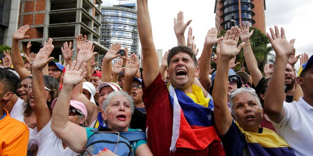 Anti-government protesters cheer after Juan Guaido, head of Venezuela's opposition-run congress, declares himself interim president of the South American country until new elections can be called, at a rally demanding the resignation of President Nicolas Maduro, in Caracas, Venezuela, Wednesday, Jan. 23, 2019.