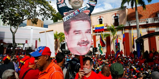 "A supporter of Venezuela's President Nicolas Maduro carries a ""Yankee Go Home"" sign in Caracas on Wednesday. (AP Photo/Ariana Cubillos)"