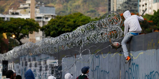 Anti-government protesters tear off razor wire from a wall surrounding a vacant lot, to make a barricade during clashes against the Venezuelan Bolivarian National Guard in Caracas. (AP Photo/Fernando Llano)