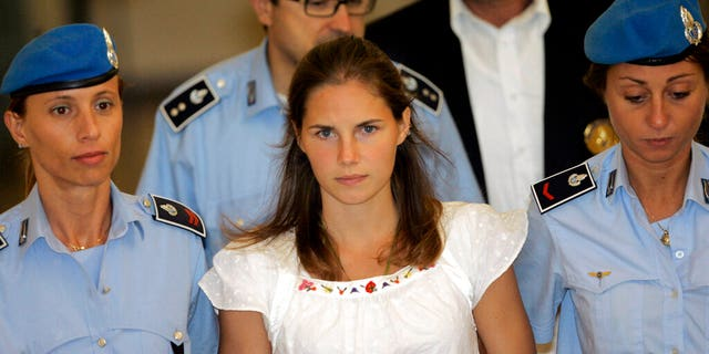 FILE: American murder suspect Amanda Knox, center, is escorted by Italian penitentiary police officers from Perugia's court after a hearing in central Italy in 2008.