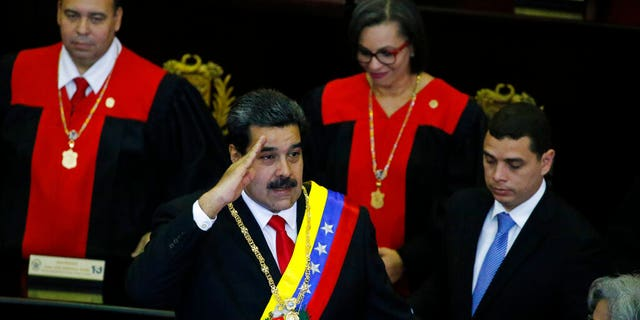 Venezuelan President Nicolas Maduro salutes as he arrives to the Supreme Court for an annual ceremony that marks the start of the judicial year in Caracas, Venezuela, Thursday, Jan. 24, 2019. Venezuelans are heading into uncharted political waters after the young leader of a newly united opposition claimed Wednesday to hold the presidency and Maduro dug in for a fight with the Trump administration. (AP Photo/Ariana Cubillos)