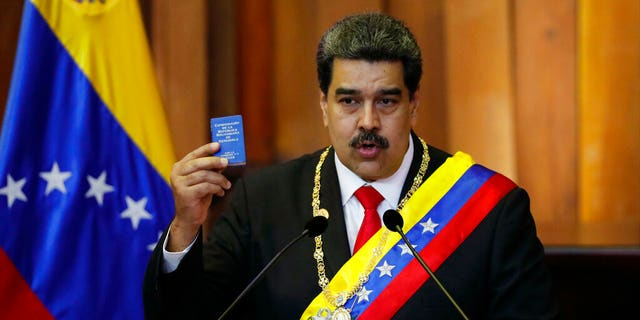In this Jan. 10, 2019, file photo, Venezuela's President Nicolas Maduro holds up a small copy of the constitution as he speaks during his swearing-in ceremony at the Supreme Court in Caracas, Venezuela.