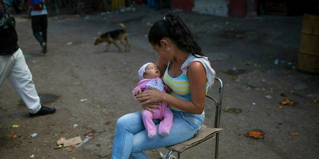 A woman playing with her 2-month-old daughter while accompanying her husband, a vegetable vendor, at a wholesale food market in Caracas, Venezuela, on Monday. (AP Photo/Rodrigo Abd)