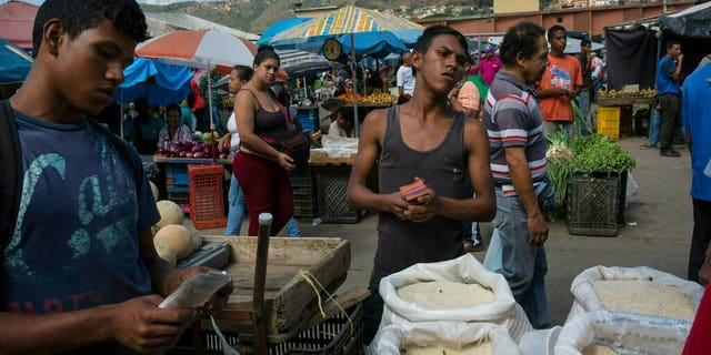 Workers are waiting for customers at their wholesale market in Caracas on Monday. (AP Photo / Rodrigo Abd)