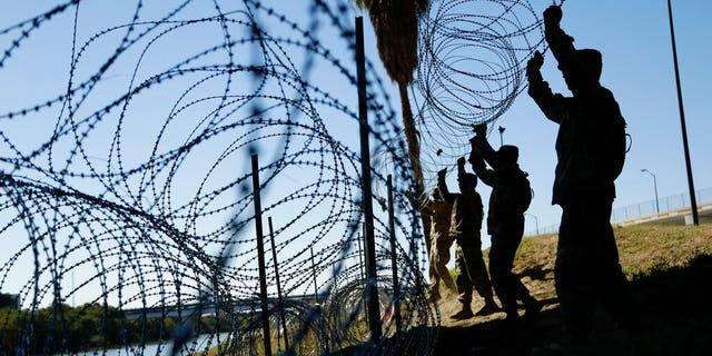 FILE - In this Nov. 16, 2018, file photo, members of the U.S. military install multiple tiers of concertina wire along the banks of the Rio Grande near the Juarez-Lincoln Bridge at the U.S.-Mexico border in Laredo, Texas. Acting Defense Secretary Pat Shanahan says the U.S. will be sending