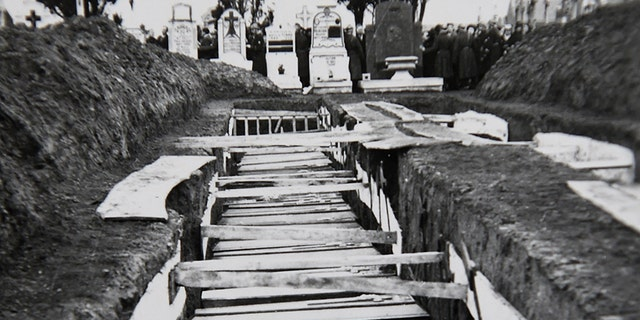 A photo taken on Decembre 5, 2018 in Villeneuve-d'Ascq, northern France, shows a reproduction of a photograph showing coffins after the massacre of Ascq in 1944 during WWII.