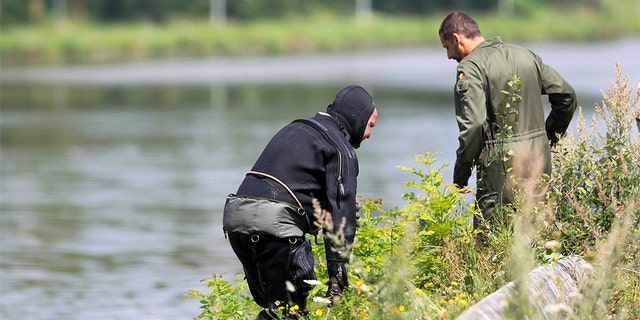 """A diver gets out of the canal in Ronquieres, some 20 milessouth of Brussels on August 3, 2010 during a search for evidence in the """"Brabant's killers"""" case."""