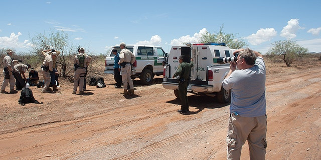Howard Buffett photographing a border patrol apprehension in a desert area in Arizona.