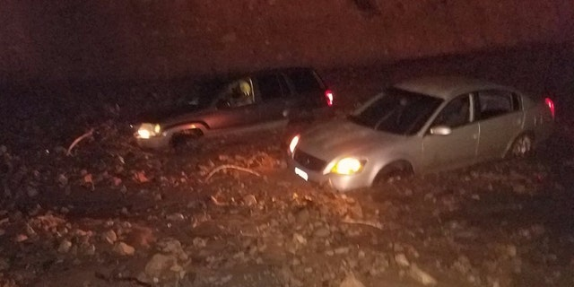 Vehicles became trapped on the Pacific Coast Highway after mudslides on Saturday due to heavy rain in wildfire burn areas.