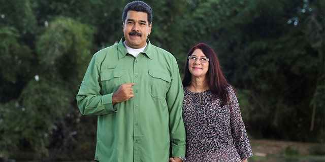 Venezuela's President Nicolas Maduro (L) and his wife and deputy of Venezuela's United Socialist Party (PSUV) pose for a photo during the recording of a government Christmas message in Caracas, Venezuela December 20, 2016.