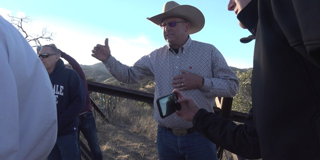 A rancher shows the congressmen and their staff a part of his ranch on the border where sticks, steel, and barbed wire separate his ranch from Mexico.