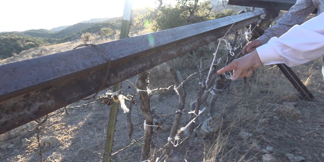 A rancher shows the congressmen and their staff a part of his ranch on the border where sticks, steel, and barbed wire seperate his ranch from Mexico.