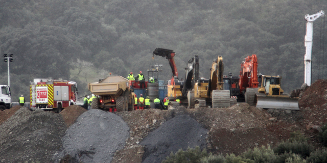 In this photo taken on Sunday, Jan. 20, 2019, drill and excavating machinery work on top of the mountain next to a deep borehole to reach a 2-year-old boy trapped there for six days near the town of Totalan in Malaga, Spain. Spanish officials say rescuers are making slow progress in exceptionally difficult conditions to reach a 2-year-old boy who fell into a narrow, deep borehole in the countryside eight days ago.