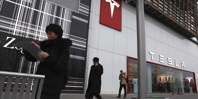 Residents walk past a Tesla store in Beijing, China, Monday, Jan. 7, 2019. Tesla Motors CEO Elon Musk said Monday on twitter that the automaker is breaking ground for a Shanghai factory and will start production of its Model 3 by the end of the year. (AP Photo/Ng Han Guan)