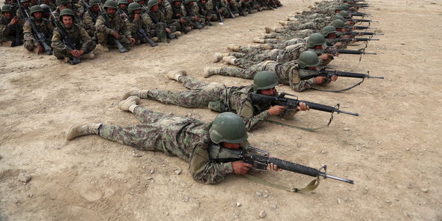 In this Oct. 31, 2018, photo, Afghan National Army (ANA) soldiers carry out an exercise during a live firing at the Afghan Military Academy in Kabul, Afghanistan.