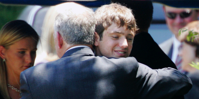 In this June 29, 2006, file photo, John Ramsey hugs his son, Burke, facing the camera, at the graves of his wife, Patsy, and daughter JonBenet, during services for his wife at the St. James Episcopal Cemetery in Marietta, Ga. A $750 million defamation lawsuit filed against CBS by Burke Ramsey, the brother of JonBenet Ramsey, has been settled on Wednesday, Jan. 2, 2019. The Daily Camera reports court records show that a Michigan Circuit Court judge dismissed the lawsuit filed by Burke Ramsey in December 2016. — AP Photo/Ric Feld, File