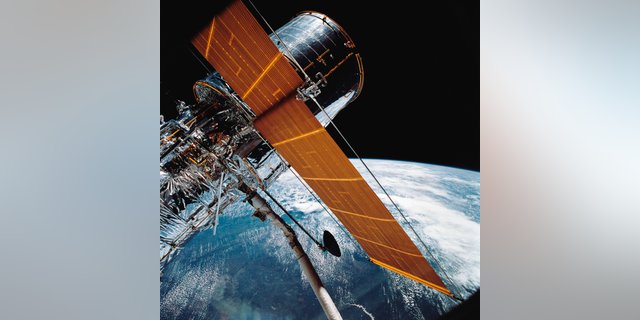 In this April 25, 1990 photo, most of the giant Hubble Space Telescope can be seen as it is suspended in space by Discovery's Remote Manipulator System (RMS) following the deployment of part of its solar panels and antennae.