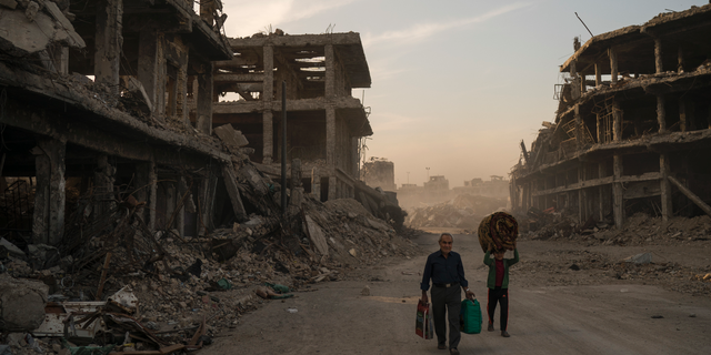 In this Nov. 15, 2017 file photo, Haider, left, and Abdullah carry belongings they collected from their damaged house to wash before returning to live in the Old City of Mosul, Iraq. (AP Photo/Felipe Dana)