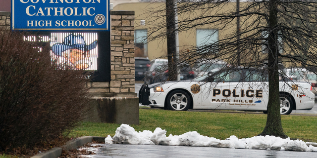A police car sits at the entrance to Covington Catholic High School in Park Hills, Ky., Saturday, Jan 19, 2019. The school has been besieged by threats of violence and was closed for safety reasons on Tuesday, after viral videos misrepresented the actions of its students at a pro-life march.  (AP Photo/Bryan Woolston)