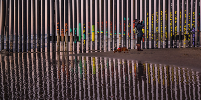 FILE - In this Jan. 3 photo, a woman at the border fence between San Diego and Tijuana, as seen from Mexico. The top House Republican says a bipartisan border security compromise that Congress hopes to produce doesn't have to include the word