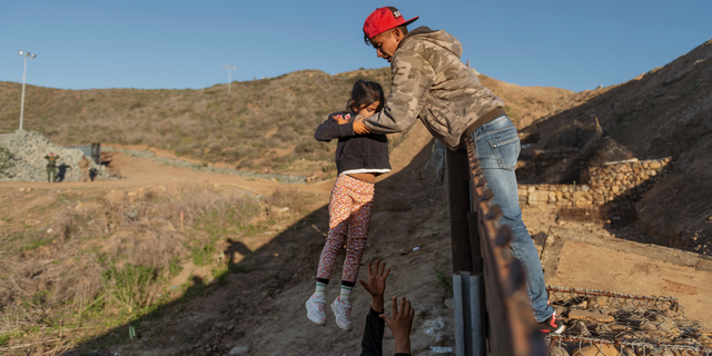 A migrant from Honduras pass a child to her father after he jumped the border fence to get into the U.S. side to San Diego, Calif., from Tijuana, Mexico, Thursday, Jan. 3, 2019. Discouraged by the long wait to apply for asylum through official ports of entry, many migrants from recent caravans are choosing to cross the U.S. border wall and hand themselves in to border patrol agents. (AP Photo/Daniel Ochoa de Olza)