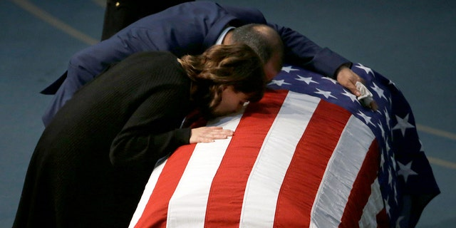 Lupe Corona and Merced Corona kiss the flag-draped coffin of their daughter, Davis Police Officer Natalie Corona, during funeral services for Natalie Corona at the University of California, Davis, Friday, Jan. 18, 2019, in Davis, Calif. (Associated Press)
