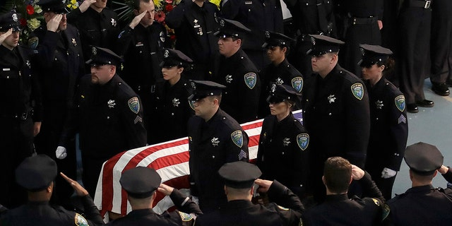 Davis Police officers salute the flag-draped coffin of Davis Police Officer Natalie Corona after funeral services for Corona at the University of California, Davis, Friday, Jan. 18, 2019, in Davis, Calif. (Associated Press)