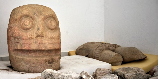 In this 2018 photo provided by Mexico's National Institute of Anthropology and History, INAH, a skull-like stone carving and a stone trunk depicting the Flayed Lord, a pre-Hispanic fertility god depicted as a skinned human corpse, are stored after being excavated. (Meliton Tapia Davila/INAH via AP)