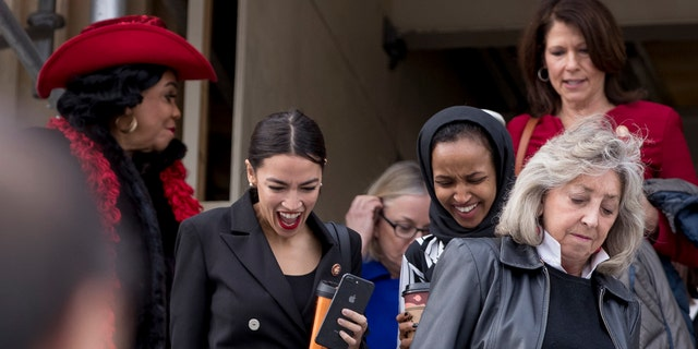From left, Rep. Frederica Wilson, D-Fla., Rep. Alexandria Ocasio-Cortez, D-N.Y., Rep. Ilhan Omar, D-Minn., Rep. Cheri Bustos, D-Ill., and Rep. Dina Titus, D-Nev., walk down the House steps to take a group photograph of the House Democratic women members of the 116th Congress on the East Front Capitol Plaza on Capitol Hill in Washington, Friday, Jan. 4, 2019, as the 116th Congress begins. (AP Photo/Andrew Harnik)