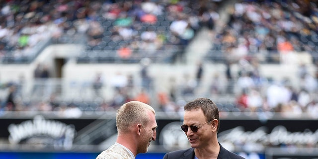 Veteran Rob Jones talks with actor Gary Sinise after throwing out the first pitch during Military Opening Day before an inter-league baseball game between the Detroit Tigers and the San Diego Padres at Petco Park April 13, 2014 in San Diego, California.