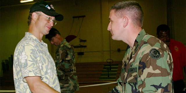 """Actor Gary Sinise shakes the hand of Army Capt. Marc Melton at Fort Polk Army Post on June 24, 2004 in Fort Polk, Louisiana. Sinise performed with his touring band called """"The Lt. Dan Band"""" named after the character he portrayed in the movie """"Forest Gump."""""""