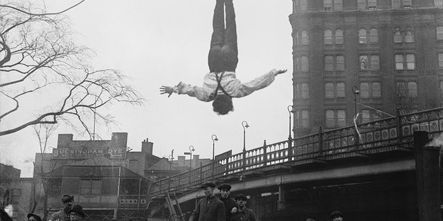 Harry Houdini hangs upside down from a crane after freeing himself from a straitjacket.