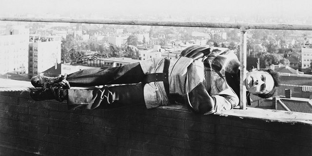 Harry Houdini holds onto a railing by his chin while tied up in a straight jacket.