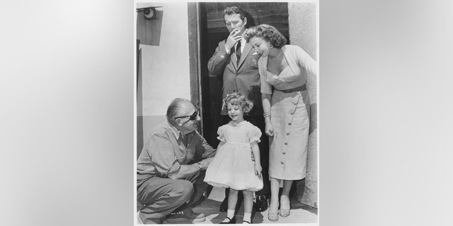 """Director Fritz Lang with child actress Bridget Duff on the set of the 1956 movie """"While the City Sleeps."""" Actor Howard Duff (smoking) and actress Ida Lupino play Bridget's parents in the movie."""