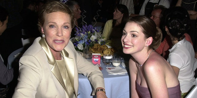 "Julie Andrews, left, clutches Anne Hathaway's hand at an after following the premiere of ""The Princess Diaries"" at El Capitan Theatre on July 29, 2001, in Hollywood, Calif."