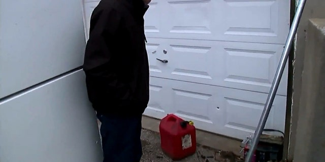 Donald Clark shows where a bullet pierced his garage in Kansas City, Mo. after celebratory gunfire on New Year's Day.