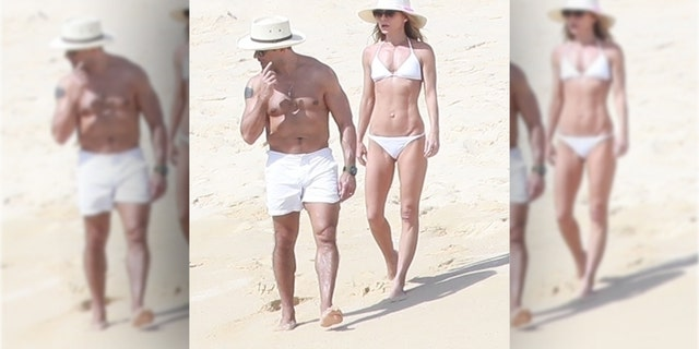 The mother-of-three showed off her rock hard body in a tiny white bikini while strolling along the sand with hubby Mark Consuelos.